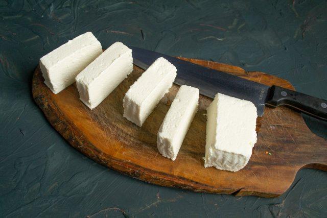 Брусок адыгейского сыра нарезаем ломтиками толщиной примерно 1.5-2 сантиметра