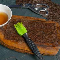 Кладём нори на доску, кулинарной кисточкой смачиваем соевым рассолом
