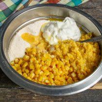 В миску выкладываем кукурузные зёрна, баночку измельченной кукурузы, добавляем сухие ингредиенты и сметану