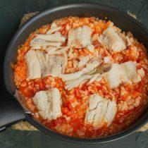 Перемешиваем томатный соус с рисом, солим и выкладываем сверху припущенное филе минтая