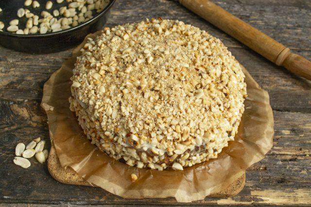 Покрывает торт толстым слоем рубленого арахиса