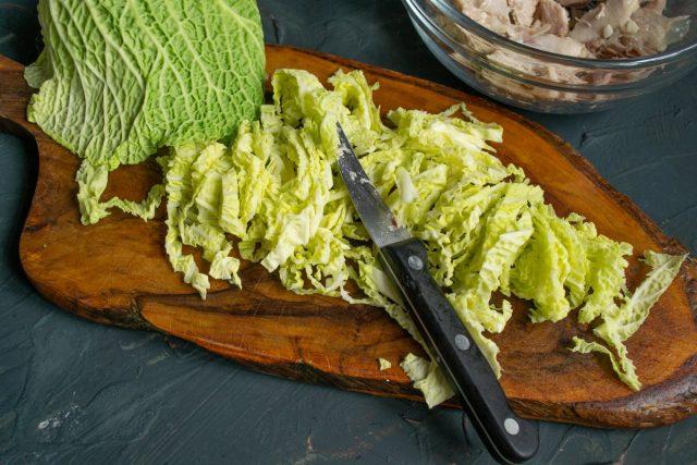 Листья савойской капусты сворачиваем в трубочку, шинкуем тонкими полосками