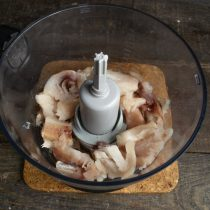 В чашу кухонного комбайна кладём порезанное крупно филе минтая
