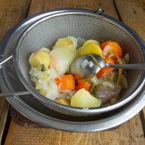 Достаём курицу из кастрюли, процеживаем бульон, перекладываем овощи в сито