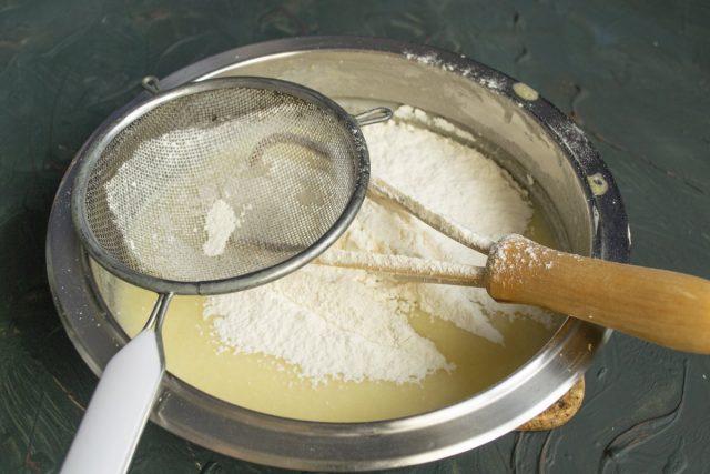 Смешиваем муку с содой и пекарским порошком, просеиваем в миску с жидкими ингредиентами. Замешиваем тесто