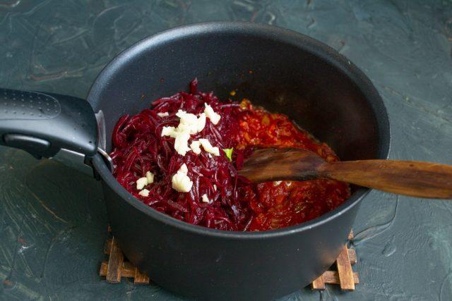 Отваренную свёклу натираем на тёрке, добавляем к овощной зажарке, добавляем измельченный чеснок