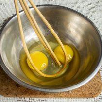 Разбиваем в отдельную миску два яйца, насыпаем соль и сахарный песок, смешиваем венчиком