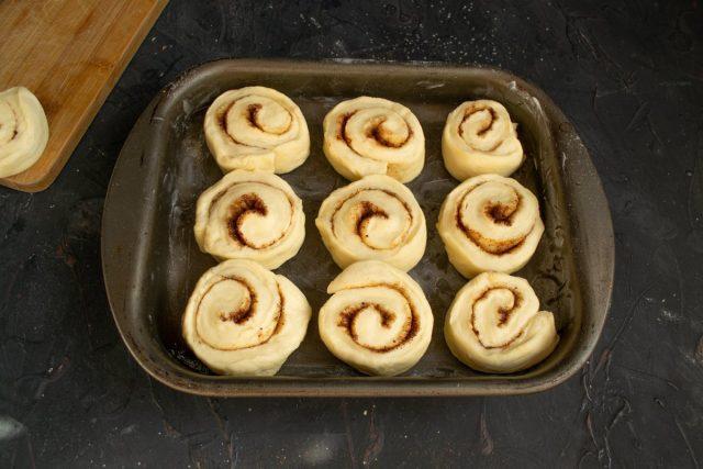 Нарезаем рулет на булочки, выкладываем в смазанный маслом противень, оставляем на расстойку