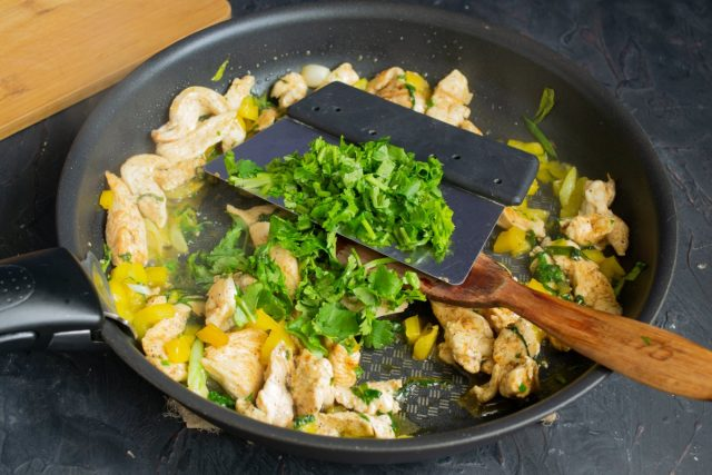 Добавляем петрушку или кинзу, готовим курицу с овощами 3-4 минуты, снимаем сковороду с огня и посыпаем блюдо морской солью