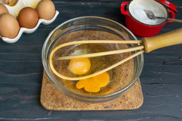 В миску разбиваем куриные яйца, солим, взбиваем венчиком