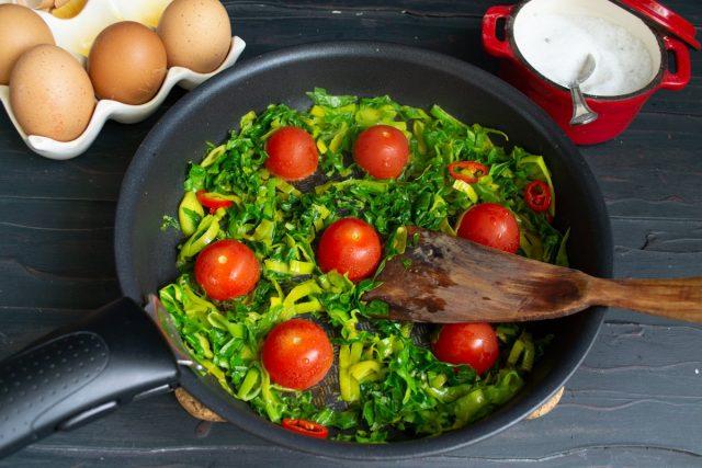 Обжариваем зелень 2 минуты, добавляем половинки помидоров, кладём их срезом вниз