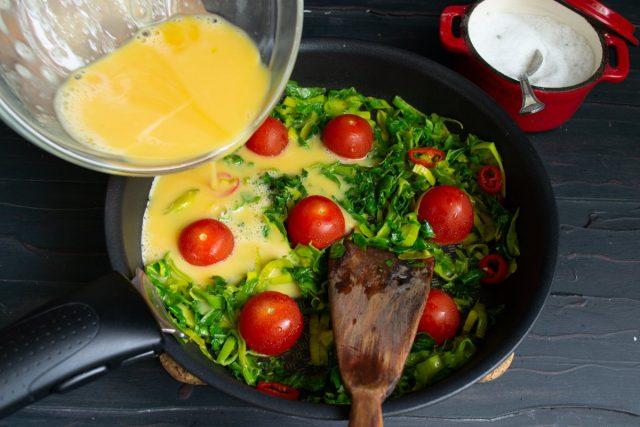 Вливаем яично-молочную смесь, накрываем сковороду крышкой и готовим омлет на маленьком огне
