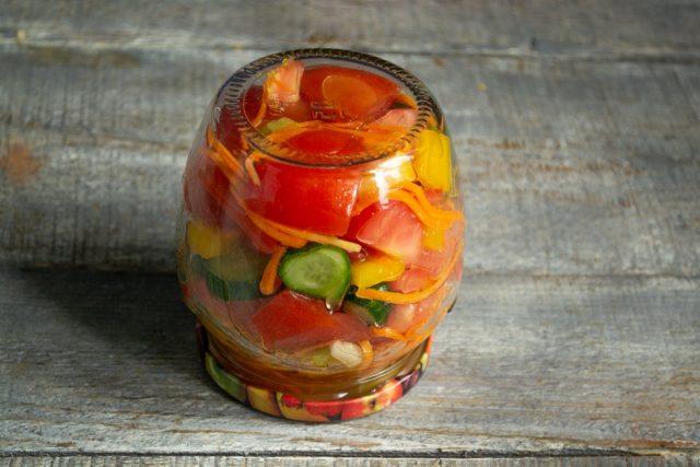 Выливаем заправку в банку, закручиваем салат из помидоров и огурцов с оливками прокипяченной крышкой