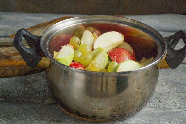 Кладём нарезанные яблоки и виноградины в кастрюлю, наливаем 50 мл воды