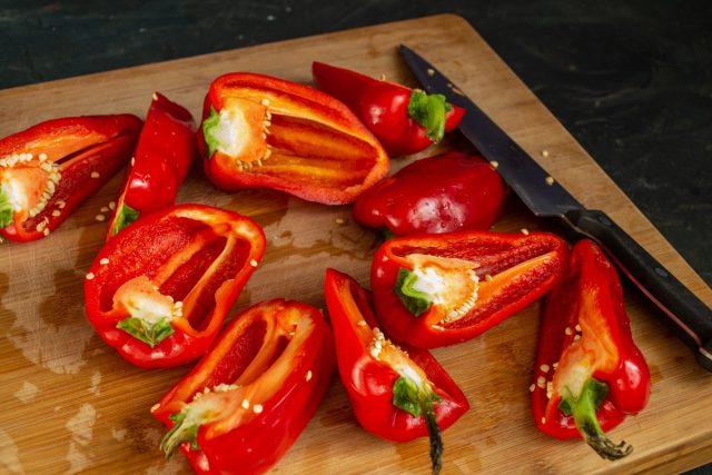 Стручки сладкого перца разрезаем пополам, очищаем от плодоножек и семян