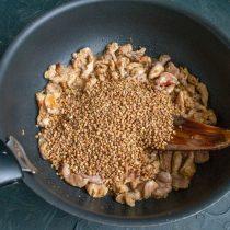 Насыпаем сухую гречневую крупу, жарим вместе с мясом 5 минут