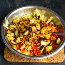 Кладём тушеные овощи и обжаренные баклажаны