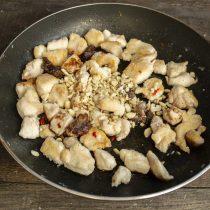 Добавляем в сковороду рубленые орехи, по вкусу солим, перчим