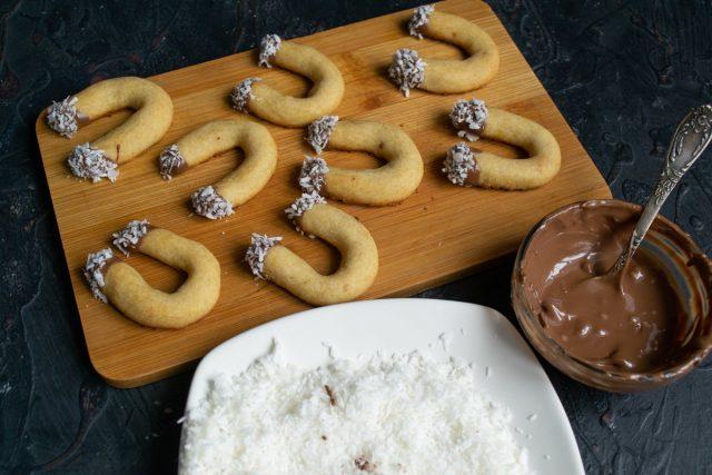 Обмакиваем края печенья в растопленный шоколад, затем сразу обмакиваем в кокосовую стружку