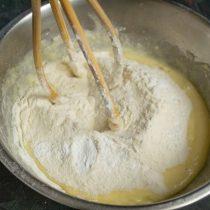 Перемешиваем муку и разрыхлитель, просеиваем в миску с жидкими и замешиваем тесто