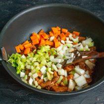 Добавляем лук и чеснок, обжариваем овощи с мясом примерно 10 минут