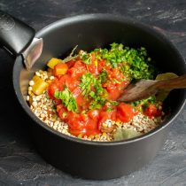 Добавляем консервированные помидоры и измельченный пучок петрушки