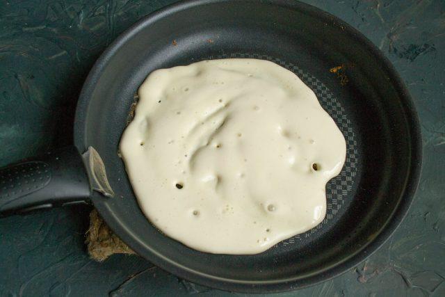 На разогретую сковороду выкладываем 2-3 ст. л. теста, аккуратно разравниваем лопаткой