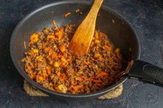 Добавляем морковь, нарезанный помидор, томатную пасту, приправляем и готовим мясо еще 10 минут
