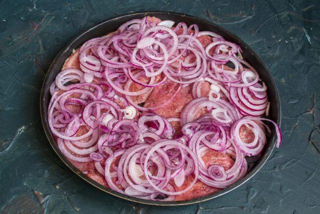 Выкладываем мясо в форму в один слой, на мясо кладём луковые кольца