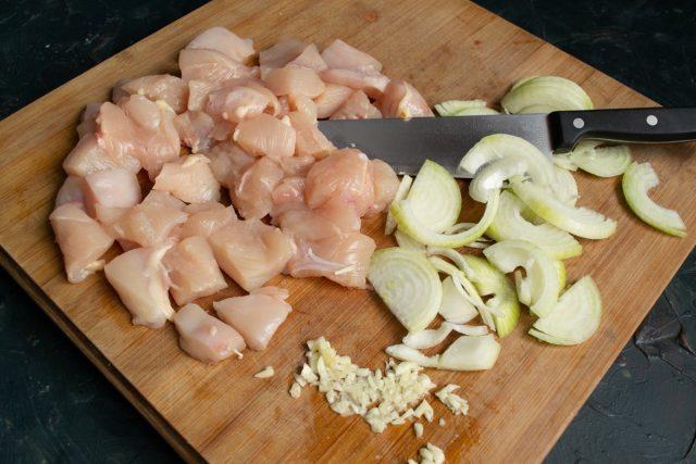 Нарезаем филе куриной грудки, репчатый лук и зубчики чеснока
