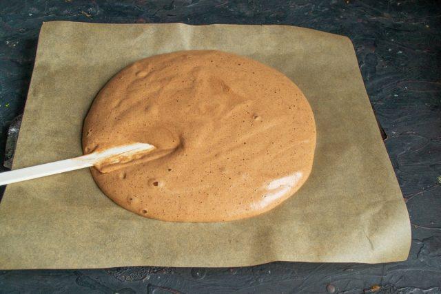 На противень кладём лист силиконовой бумаги для выпечки, выкладываем тесто и разравниваем