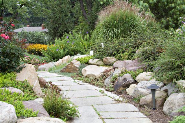 Сочетание камня в оформлении изгороди и дорожки на участке