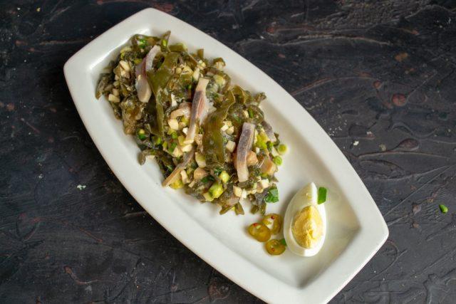 Выкладываем салат на овальную тарелку, рядом кладём ломтик варёного яйца и маринованный чили