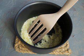 В кастрюлю наливаем оливковое масло, добавляем нарезанный лук и обжариваем