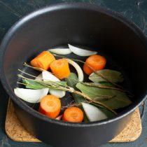Кладём в кастрюлю луковицу, добавляем морковь, лавровый лист, листья порея, черный перец и корешок петрушки