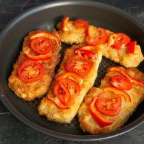 Выкладываем на мясо ломтики помидоров и полоски перца