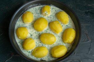 Выкладываем клубни картофеля в форму и выливаем соус