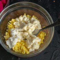 Желтки разминаем вилкой, добавляем творожный сыр, майонез, соль, перец и чеснок