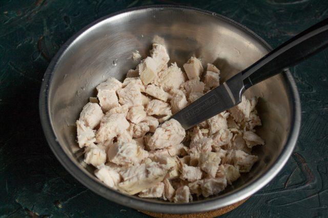 Варёное куриное филе нарезаем кубиками или разрываем на волокна