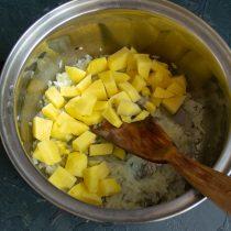 Добавляем к обжаренному луку нарезанную кубиками картошку