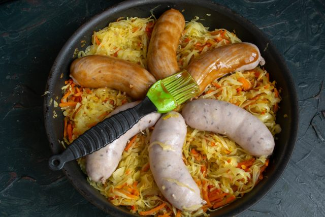 За 5 минут до готовности достаём блюдо из духовки и смазываем колбаски глазурью