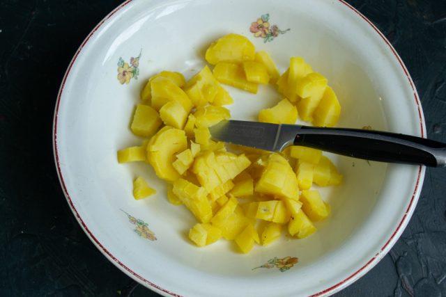 Сваренный картофель нарезаем кубиками и кладём в салатник