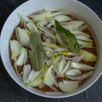 На гречку кладём нарезанный лук, добавляем лавровый лист и черный перец