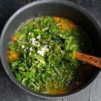 Добавляем нарезанную крапиву и чеснок, снова доводим суп до кипения и варим 5 минут