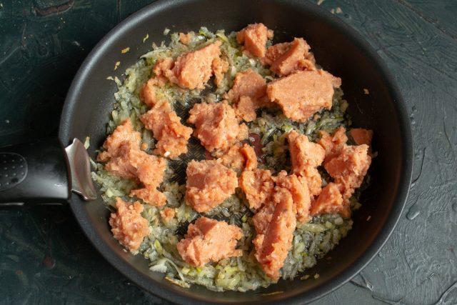 Фарш из лосося положите в сковороду к тёплому луку, жарить не нужно