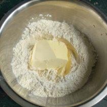 Муку просеиваем вместе с разрыхлителем теста, добавляем размягченное сливочное масло