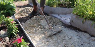 Выровняйте поверхность. Затем проведите трамбовку почвы. Обустройте дренажный слой и сделайте подушку из песка