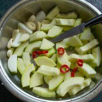 Нарезанный кабачок кладём в сотейник, добавляем лук, чеснок и чили