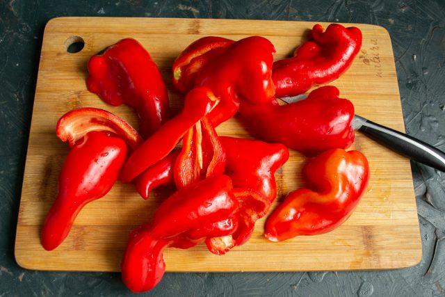 Красный болгарский перец разрезаем пополам, вырезаем плодоножку с семенами.
