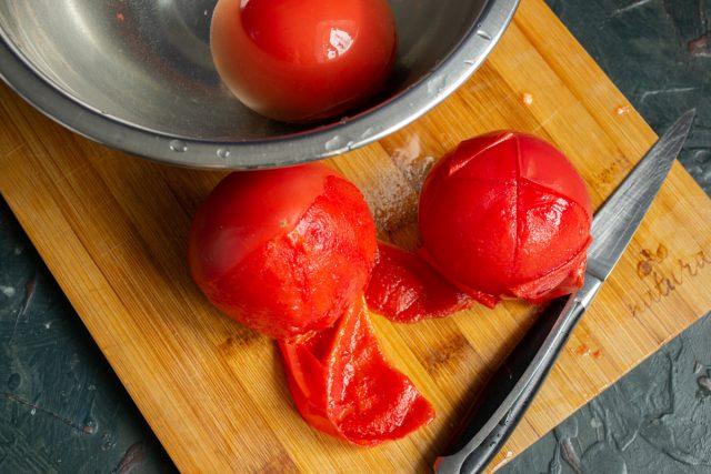 Разрезаем очищенные помидоры, вырезаем плодоножки